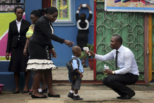 A school official takes a pupil's temperature using an infrared digital laser thermometer in front of the school premises, at the resumption of private schools, in Lagos, in this September 22, 2014 file photo. (Photo by Akintunde Akinleye/Reuters)