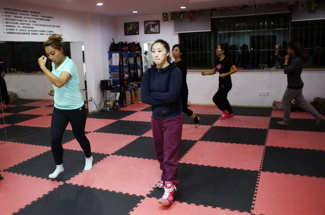 Gong Jin (C), founder of Princess Women's Boxing Club, teaches a boxing class at her boxing club in downtown Shanghai December 8, 2014. (Photo by Carlos Barria/Reuters)