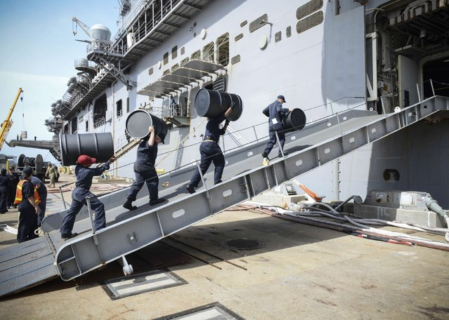 Sailors move supplies aboard the amphibious assault ship USS Iwo Jima (LHD 7) during an onload of more than 500 Marines from the 24th Marine Expeditionary Unit (24th MEU) and nearly 300 pallets of supplies, awaiting further tasking at Naval Station Norfolk, Virginia, U.S., on October 7, 2016 as Hurricane Matthew left flooding and wind damage in Florida before moving north to soak coastal Georgia and the Carolinas. (Photo by Courtesy Jess E. Toner/Reuters/U.S. Navy)