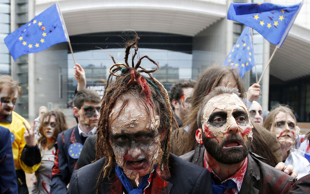 """Demonstrators, including members of the European Parliament (MEP), dressed as zombies, dance to the music of Michael Jackson's """"Thriller"""" while participating in a flash-mob in front of the EU Parliament in Brussels. The flash-mob was organized in protest against possible EU-India free trade agreements that could endanger access to medicines, organisers said. (Photo by Francois Lenoir/Reuters)"""