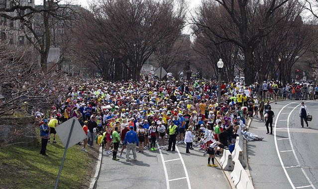 Runners who had not yet finished the race are stopped before the Massachusetts Avenue overpass on Commonwealth Avenue following the explosions. (Photo by Yoon S. Byun/The Boston Globe)