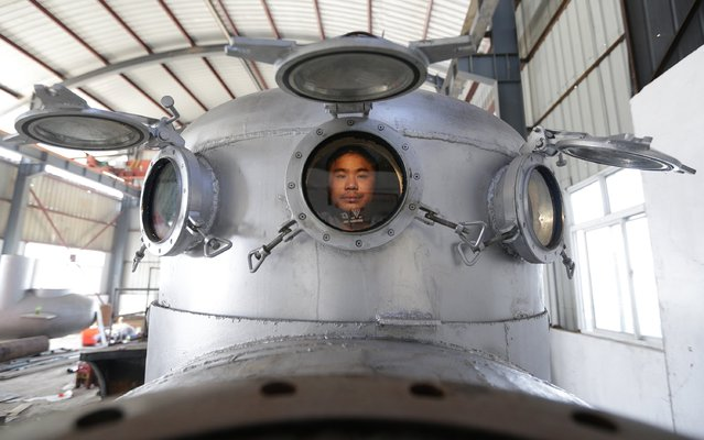 Zhang Wuyi sits in his newly made multi-seater submarine at his new workshop near an artificial pool in Wuhan, Hubei province, November 14, 2012. Zhang, a 37-year-old local farmer, who is interested in scientific inventions, has independently made seven miniature submarines with several fellow engineers, one of which was sold to a businessman in Dalian at a price of 100,000 yuan ($15,855) last October. (Photo by Reuters/Stringer)