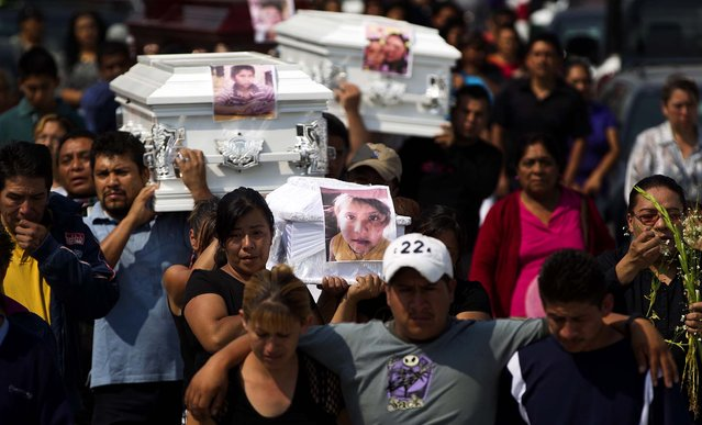 Friends and family carry coffins containing the remains of victims of a gas tanker explosion in a funeral procession in Ecatepec, a Mexico City suburb, on May 8, 2013. A natural gas tanker truck lost control, hit a center divider and exploded on a highway lined by homes in the Mexico City suburb early Tuesday, killing at least 20 people and injuring nearly three dozen, authorities said. (Photo by Eduardo Verdugo/Associated Press)