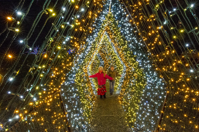 """Two children walk past 200,000 lights that decorate a winter wonderland where people walk through at Naumkeag, part of the land managed by the Trustees of Reservations, in Stockbridge, Massachusetts on December 13, 2020. The town, recently voted the number one Christmas town in the US, is also known for Norman Rockwell's painting of the town's Main Street during Christmas in """"Home for Christmas"""" (Stockbridge Main Street at Christmas) 1967. (Photo by Joseph Prezioso/AFP Photo)"""