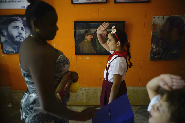Back-dropped with pictures of the late Fidel Castro and President Raul Castro a school girl and a school boy raise their hands to confirm a vote as a woman casts her ballot for municipal elections in Havana, Cuba, Sunday November 26, 2017. The elections were postponed by a month to Nov. 26 after Hurricane Irma devastated part of the island last September. (Photo by Ramon Espinosa/AP Photo)