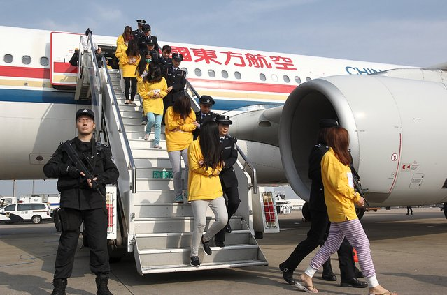 Suspects involved in telecom fraud walk off a plane after being repatriated from overseas, at an airport in Shanghai, China, November 10, 2015. (Photo by Reuters/China Daily)
