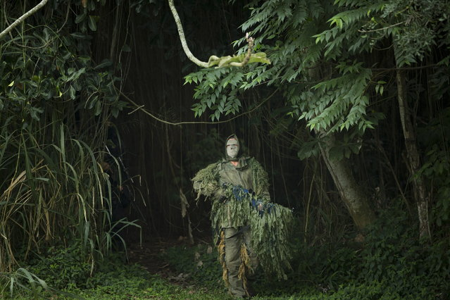 A Brazilian Navy sniper participates in a mock hostage rescue drill in Rio de Janeiro, Brazil,  Monday, May 27, 2013. The Brazilian Navy conducted the drill in preparation for the Confederation Cup that runs from June 15–30. (Photo by Victor R. Caivano/AP Photo)