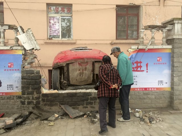 Pedestrians look at a car which fell into a pit after crashing through a brick wall, on a hazy day in Xianyang, Shaanxi province, China, November 30, 2015. (Photo by Reuters/Stringer)