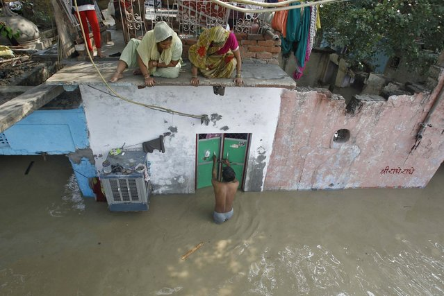 A man unlocks the door of his flooded house as other residents watch after a rise in the water level of river Yamuna in New Delhi, June 19, 2013. (Photo by Anindito Mukherjee/Reuters)
