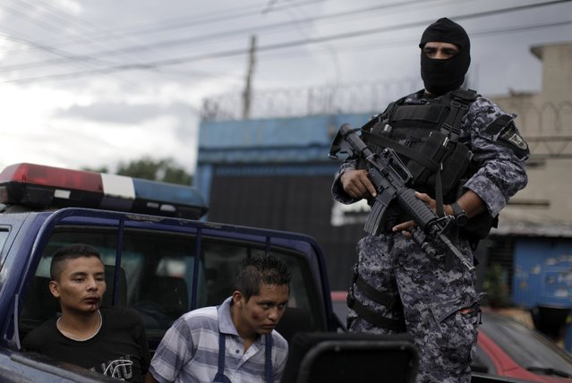 A police officer stands guard next to alleged gang members who are accused of killing a private security agent at the central market in San Salvador October 8, 2014. (Photo by Jose Cabezas/Reuters)