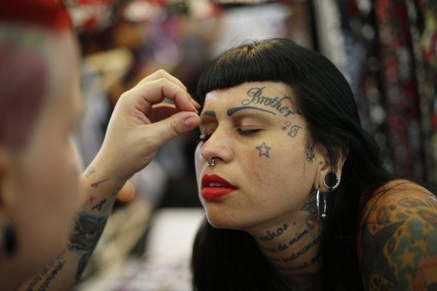 A woman gets false eyelashes applied during Rio Tattoo Week in Rio de Janeiro, Brazil, Friday, January 16, 2015. (Photo by Silvia Izquierdo/AP Photo)