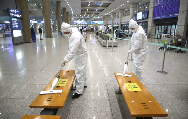 Workers wearing protective gears disinfect chairs as a precaution against the coronavirus at the arrival hall of the Incheon International Airport in Incheon, South Korea, Monday, December 28, 2020. South Korea has confirmed its first cases of a more contagious variant of COVID-19 that was first identified in the United Kingdom. (Photo by Kim Sun-woong/Newsis via AP Photo)