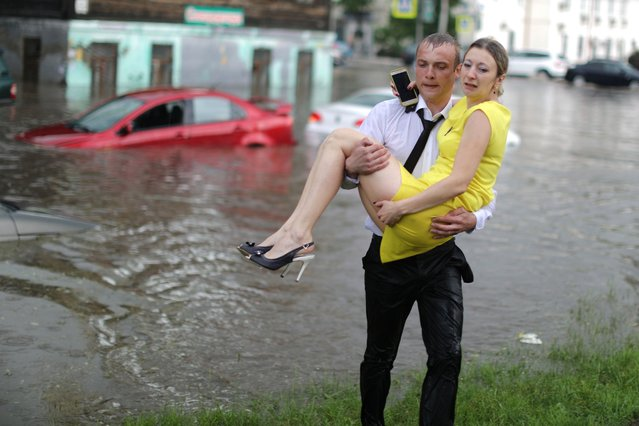 A woman is rescued from a car after a flash flood in Nizhny Novgorod, Russia on June 19, 2018. (Photo by Lucy Nicholson/Reuters)