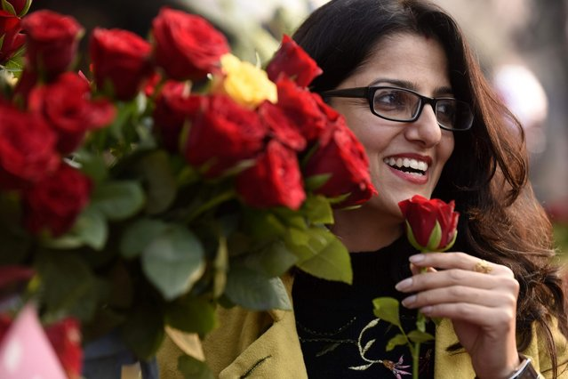 A shopper looks at roses at a flower stall on Valentine's Day in Amritsar on February 14, 2021. (Photo by Narinder Nanu/AFP Photo)