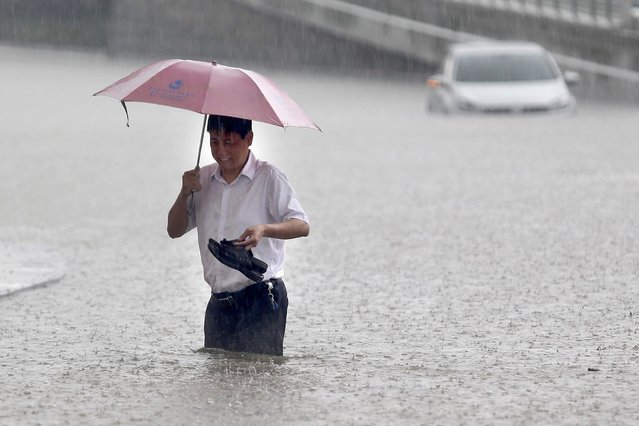 A man walking on a flooded street holding his hands in Wuhan, central China's Hubei province after a heavy storm. (Photo by AFP Photo)