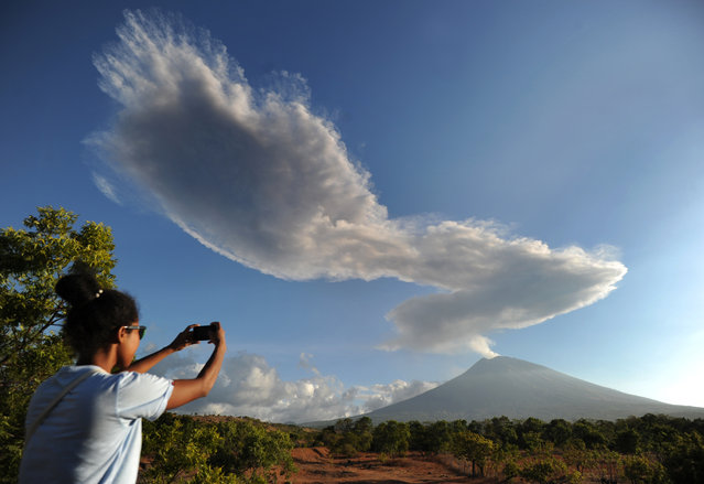A woman takes photos as Mount Agung volcano sends up another plume of smoke, seen from the Kubu subdistrict in Karangasem Regency on Indonesia's resort island of Bali on July 5, 2018. Mount Agung roared to life again on July 2, belching a plume of ash 2,000 metres (6,500 feet) high, as well as temporarily shuttering the airport and grounding hundreds of flights after erupting the week before. (Photo by Sonny Tumbelaka/AFP Photo)
