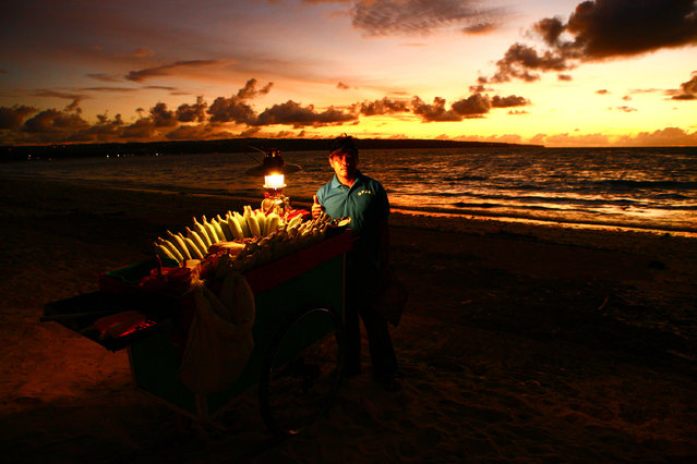 """Indonesian Man Selling Corn"". This man waited patiently on Jimbaran Beach in Bali, Indonesia to sell corn to tourists after they ate their candlelit dinners on the beach. I waited and watched how the gorgeous sunset slowly started to match the lighting of his cart of corn and then walked over and asked him to take this portrait of him. I love how he gave me the ""thumbs up"".  (Photo and caption by Laura Grier/National Geographic Traveler Photo Contest)"