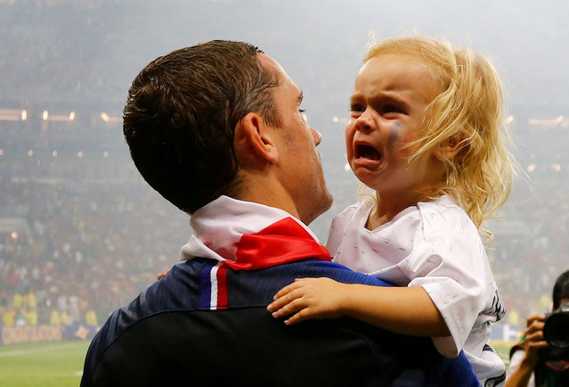 France' s forward Antoine Griezmann carries his daughter, Mia, as he celebrates after the Russia 2018 World Cup final football match between France and Croatia at the Luzhniki Stadium in Moscow on July 15, 2018. (Photo by Darren Staples/Reuters)