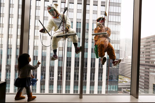 A child looks at window cleaners work while dressed in sheep (C) and monkey costumes, denoting animal signs of the Chinese zodiac calendar, during an event marking the upcoming end of the year at a hotel in Tokyo, Japan, December 21, 2015. According to the zodiac calendar, 2015 is the year of the sheep and 2016 is the year of the monkey. (Photo by Thomas Peter/Reuters)