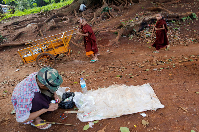 Buddhist novice monks walk past a drug user in Man Sam, northern Shan state, Myanmar July 11 , 2016. Picture taken July 11, 2016. (Photo by Soe Zeya Tun/Reuters)