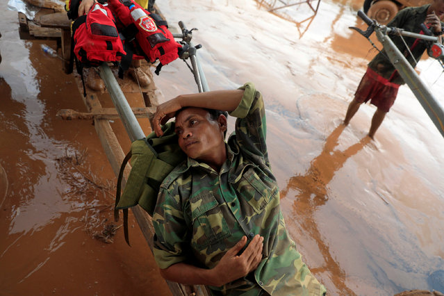 A solider rests on a locally made vehicle during the flood after the Xepian-Xe Nam Noy hydropower dam collapsed in Attapeu province, Laos on July 26, 2018. (Photo by Soe Zeya Tun/Reuters)