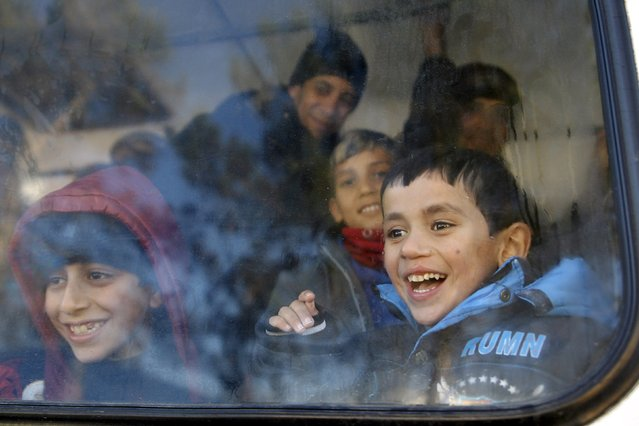 Children laugh as the Red Noses Clowndoctors entertain them before their deparuture to Austria at a registration center in Dobova, Slovenia, December 27, 2015. (Photo by Srdjan Zivulovic/Reuters)