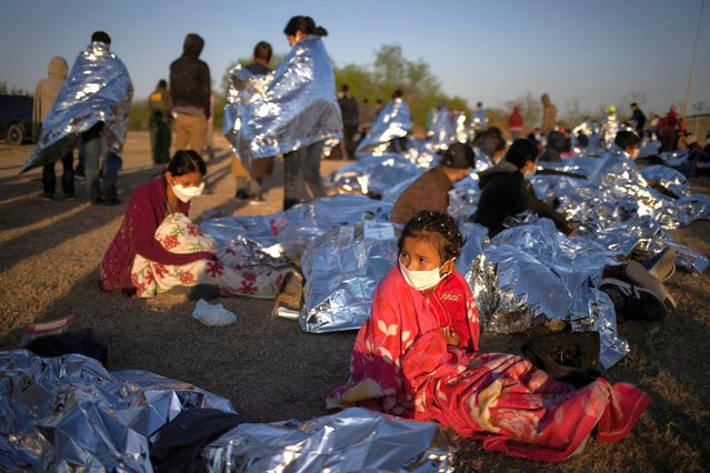 Hennessy, a four year old asylum-seeking migrant girl from Honduras, awakes at sunrise next to others who took refuge near a baseball field after crossing the Rio Grande river into the United States from Mexico on rafts, in La Joya, Texas, U.S., March 19, 2021. Emergency blankets were provided to the group of about 150 migrants from Central America by the U.S. Border Patrol agents. Hennessy's parents and siblings were sleeping nearby. (Photo by Adrees Latif/Reuters)