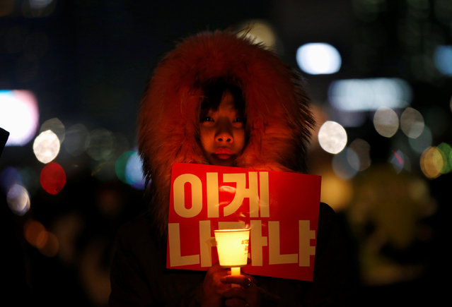 "A woman holds a candle light and a slogan at a protest calling South Korean President Park Geun-hye to step down in Seoul, South Korea, November 25, 2016. The slogan reads, ""Is this called a country?"". (Photo by Kim Hong-Ji/Reuters)"