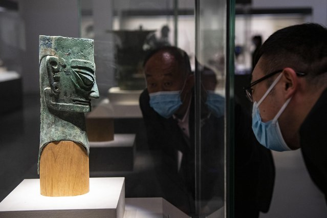 Visitors look at an ancient bronze figure statue unearthed from the Sanxingdui Ruins at the National Museum of China on March 26, 2021 in Beijing, China. The shock of hundreds of more than 3,000-year-old cultural relics newly excavated from the Sanxingdui Ruins site in SW China's Sichuan continues across China. Some stunning discoveries from the Sanxingdui Ruins preserved at the National Museum of China has drawn a number of visitors. (Photo by Hou Yu/China News Service via Getty Images)