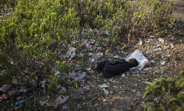 A boy takes a nap outside his house on the outskirts of Islamabad February 11, 2015. (Photo by Zohra Bensemra/Reuters)