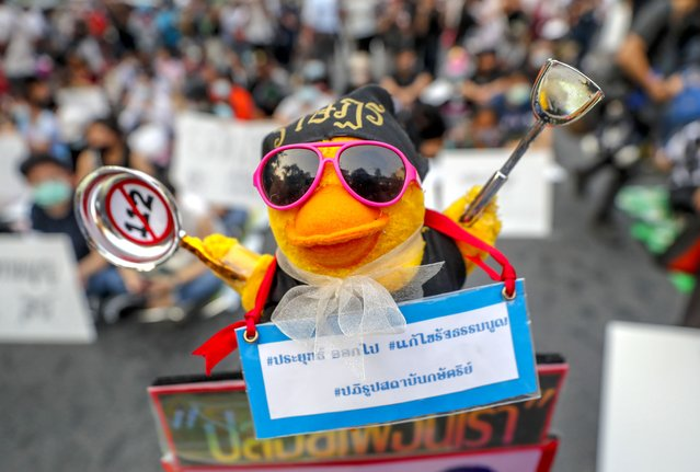 """A yellow toy duck, a recent symbol of pro-democracy protesters, has a scarf with a message attached during a rally in Bangkok, Thailand, Wednesday, March 24, 2021, ahead of an indictment against 13 protest leaders on Thursday for allegations of sedition and defaming the monarchy. Message translates as """"Prayuth get out, the constitution to be amended, the monarchy's reform"""". (Photo by Sakchai Lalit/AP Photo)"""