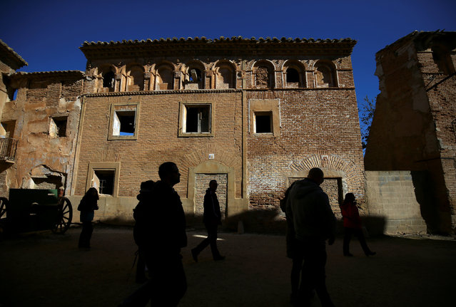 Visitors walk past ruins in the old village of Belchite, in northern Spain, November 14, 2016. (Photo by Andrea Comas/Reuters)
