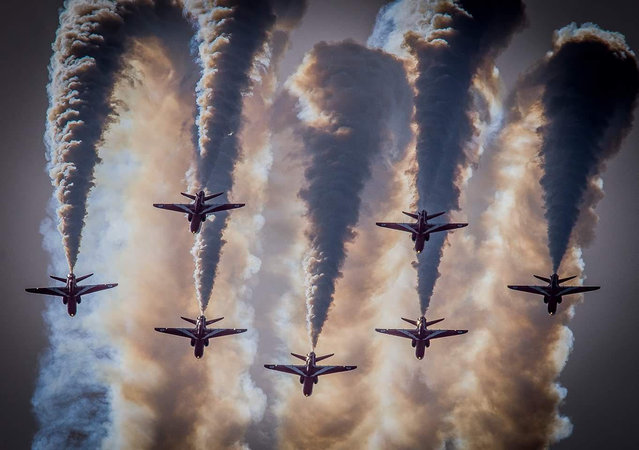 """Smoke in the Sun"". Amateur photographer, first prize: Taken at Weston air day, Weston-Super-Mare, seven of the nine Red Arrows Hawk T1 aircraft come over the top of a loop in formation. (Photo bu Mark Thompson/RAF)"