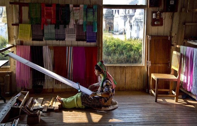 An ethnic Kayan-Padaung woman in traditional attire weaves at a souvenir shop in Ywama village, Inle Lake, northeastern Shan state, Myanmar, Monday, February 16, 2015. (Photo by Gemunu Amarasinghe/AP Photo)