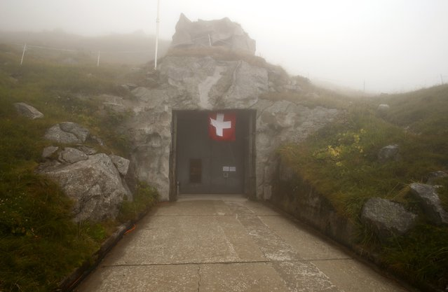 A flag flies over an entrance to the former Swiss artillery fortress Sasso da Pigna at the St. Gotthard mountain pass, Switzerland September 2, 2015. Sasso da Pigna fortress, located at 2,106 m (6,909 ft) altitude on the St. Gotthard mountain pass, was built from 1941 to 1945 and remained in military use until 1999. (Photo by Arnd Wiegmann/Reuters)
