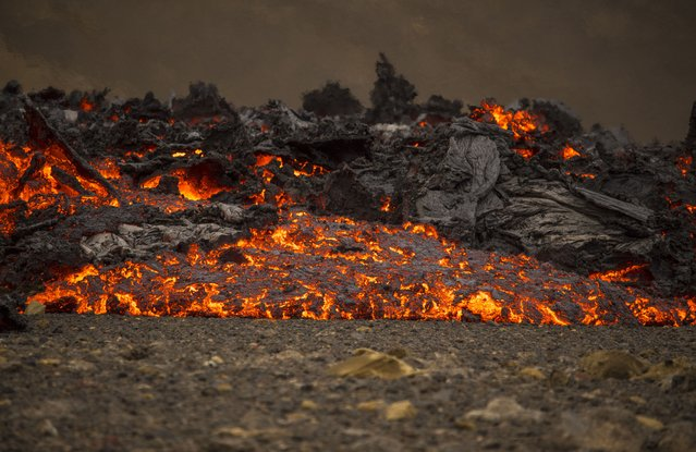 Lava flows from a new fissure on a volcano on the Reykjanes Peninsula in southwestern Iceland, Monday, April 5, 2021. (Photo by Marco Di Marco/AP Photo)