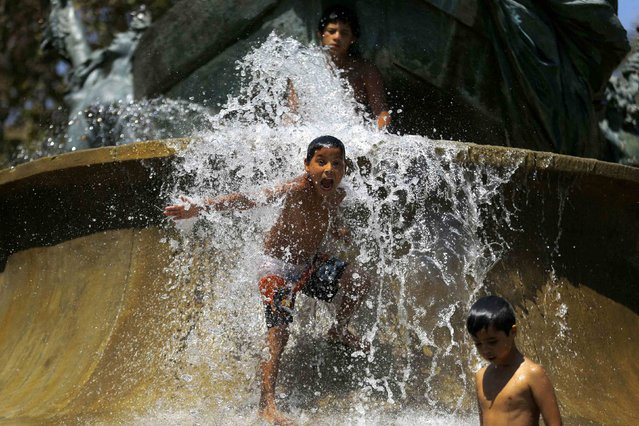 Children play in a water fountain on a hot day in Santiago, February 13, 2015. Temperatures on Friday rose up to 37 degrees Celsius (98.6 degrees Fahrenheit), according to the meteorology institute. (Photo by Ivan Alvarado/Reuters)