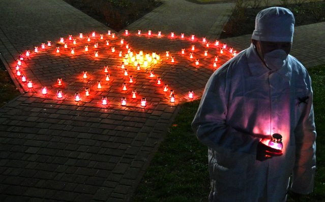 A Chernobyl plant employee holds candle near radioactivity sign at the monument to Chernobyl victims in Slavutych, the city where the power station's personnel lived, some 50 kilometres (30 miles) from the accident site on April 25, 2021, during a memorial ceremony amid the COVID-19 pandemic, caused by the novel coronavirus. Ukraine on April 26, 2021 marks the 35th anniversary of the Chernobyl disaster which was the world's worst nuclear accident. (Photo by Sergei Supinsky/AFP Photo)