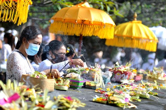 Balinese Hindus wearing protective masks offer incense as they celebrate the Galungan religious holiday at Jagatnatha temple, amid the coronavirus disease (COVID-19) pandemic, in Denpasar, Bali, Indonesia on April 14, 2021. (Photo by Nyoman Hendra Wibowo/Antara Foto via Reuters)