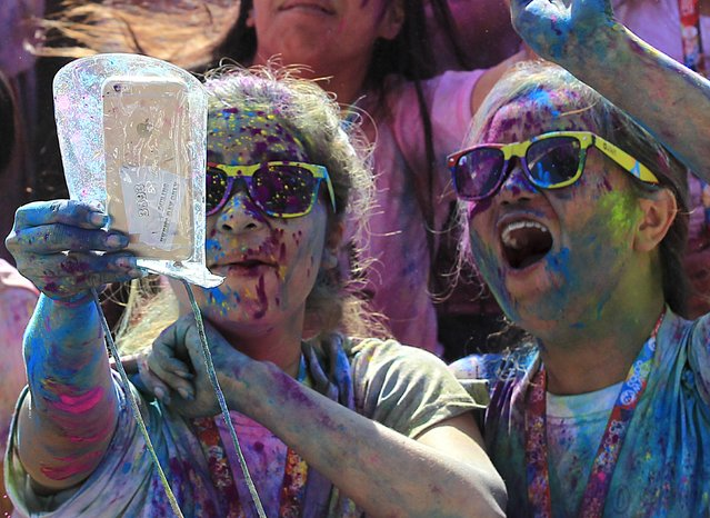 """A runner takes a selfie photo while celebrating during a """"Color Fun Run"""" in Manila, Philippines January 3, 2016. (Photo by Romeo Ranoco/Reuters)"""