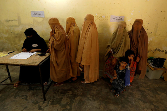 Women, clad in burqas, stand in line to cast their ballot at a polling station during general election in Peshawar, Pakistan July 25, 2018. (Photo by Fayaz Aziz/Reuters)
