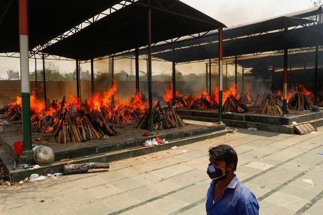 A man walks past the burning funeral pyres of those who died from the coronavirus disease (COVID-19), during a mass cremation, at a crematorium in New Delhi, India on April 26, 2021. (Photo by Adnan Abidi/Reuters)