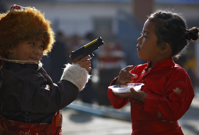 """A Tibetan boy points a toy gun towards a girl during the function organised to mark """"Losar"""" or the Tibetan New Year at a Tibetan Refugee Camp in Lalitpur February 19, 2015. (Photo by Navesh Chitrakar/Reuters)"""
