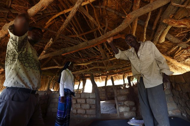 HIV-positive 71-year-old Sylverio Hachiploa (R) talks with caregivers Glandwel Muleya (L) and Sister Abigail Mwaka Mazuba (C) in his thatched hut during a visit by a home-based care team in the village of Nedwmba, south of the Chikuni Mission in the south of Zambia February 23, 2015. (Photo by Darrin Zammit Lupi/Reuters)