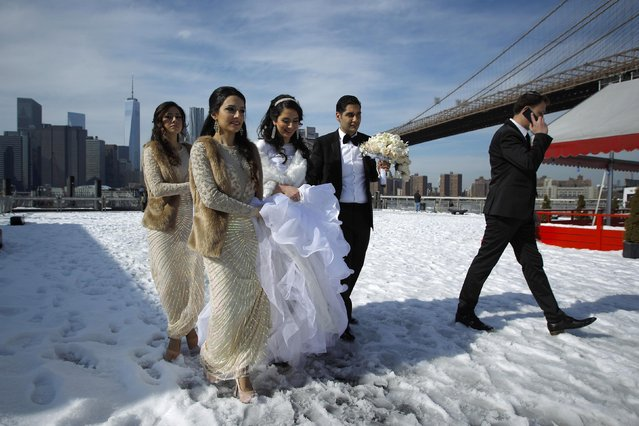 A bride (C) walks in the snow at the Brooklyn Bridge Park in New York February 22, 2015. A fresh band of winter weather that churned up the East Coast on Saturday, pummeling the storm-weary region with snow, sleet and freezing rain, was expected to gradually taper off Sunday morning, forecasters said. (Photo by Eduardo Munoz/Reuters)