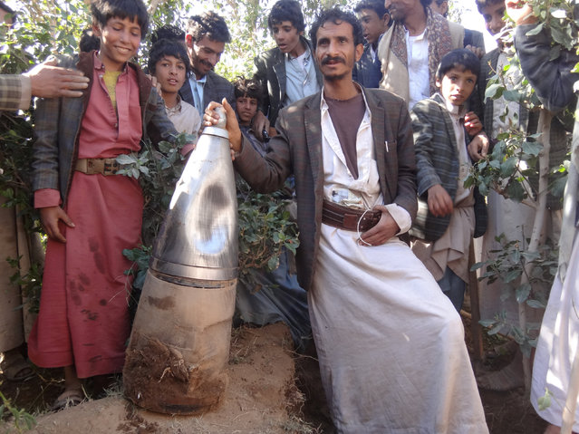 People pose for a picture next to a part of a missile they say was dropped during a Saudi-led air strike near the northwestern city of Saada, Yemen December 7, 2016. (Photo by Naif Rahma/Reuters)