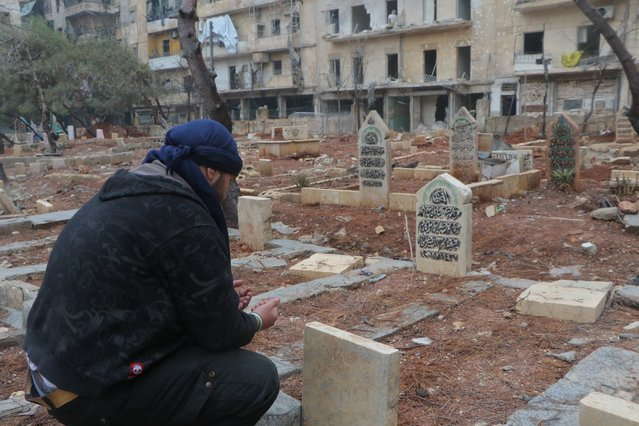 A man prays over the graves of family members in al-Mashhad neighborhood in Aleppo, Syria on December 14, 2016. (Photo by Ibrahim Ebu Leys/Anadolu Agency/Getty Images)