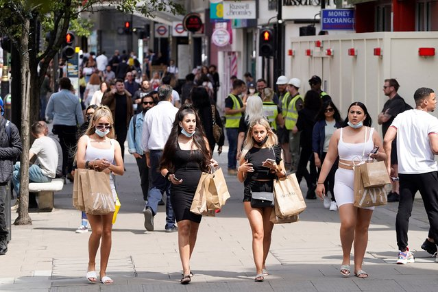 Shoppers wearing face coverings due to Covid-19, but pulled down under their chin, walk along Oxford Street in central London on June 7, 2021. The Delta variant of the coronavirus, first discovered in India, is estimated to be 40 percent more transmissible than the Alpha variant that caused the last wave of infections in the UK, Britain's health minister said Sunday. (Photo by Niklas Halle'n/AFP Photo)