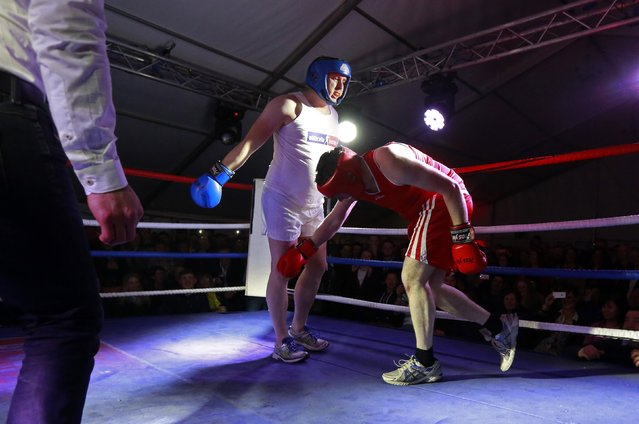 Fr Pierre Pepper (C) exchanges punches with  Jared Madden during his amateur boxing match in the town of Banagher  in County Offaly March 15, 2015. (Photo by Cathal McNaughton/Reuters)