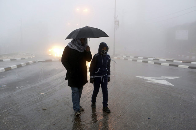 Palestinians walk in the street during a snow storm in The West Bank town of Halhul, north of Hebron, 25 Januray 2016. Stormy weather conditions across the region continued as deep storm hit the area with snow, torrential rains and strong winds. (Photo by Abed Al Hashlamoun/EPA)